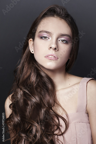 Portrait of young girl with long hair on dark background