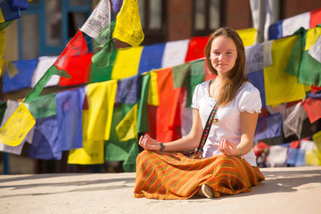 Girl sitting on Buddhist stupa, prayer flags