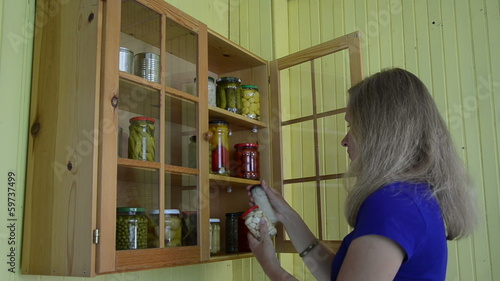 Girl take jar with pickled caper garlic and onion from cabinet