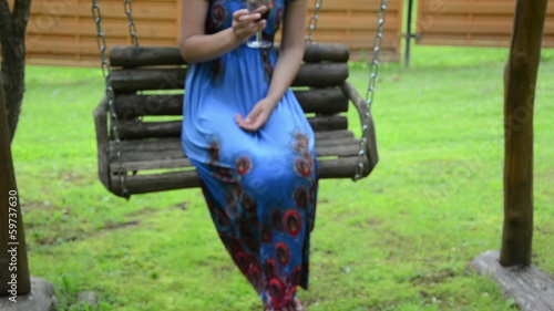 woman in blue dress with glass red vine sway in retro wood swing