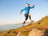 Fototapety Man practicing trail running in a coastal landscape