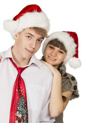 Smiling girl and the guy in red santa caps on a white isolated b
