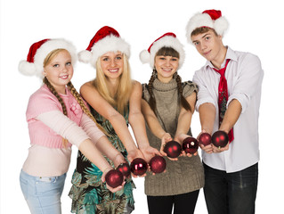 Four smiling teenagers in red christmas hats with fir-tree spher