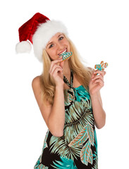Girl in red christmas hat holds gingerbread cookies in hand on w