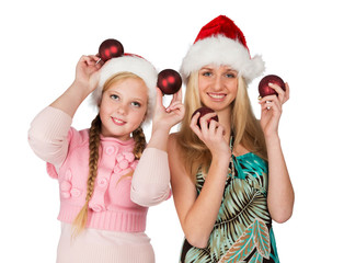 Two girls in red christmas hats hold red fir-tree spheres in han