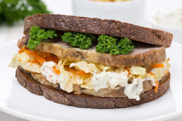 sandwich of rye bread with coleslaw and baked meat, close-up