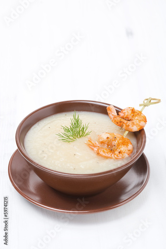 Potato cream soup with glazed shrimp on a skewer, vertical