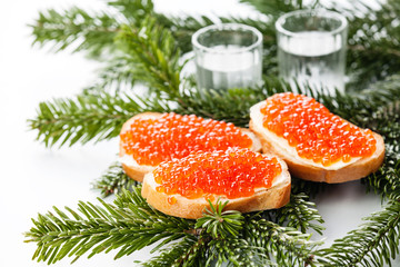 Vodka and sandwiches with red caviar on green Fir Christmas bran