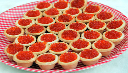 Tartlets with red caviar on a checkered plate