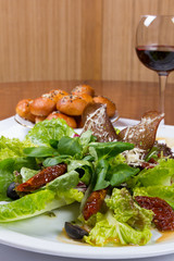 Green leafy salad with sun-dried tomatoes and parmesan cheese