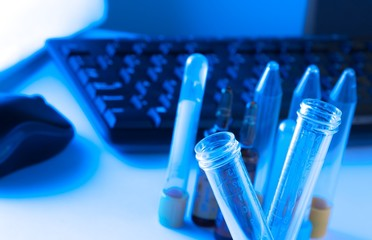 test tubes in laboratory on table near computer keyboard