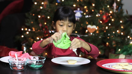Asian Girl Decorates Snowman Christmas Cookie