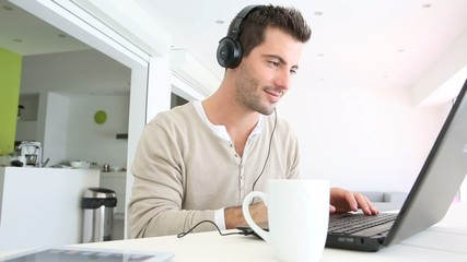 Man in font of laptop with headset on