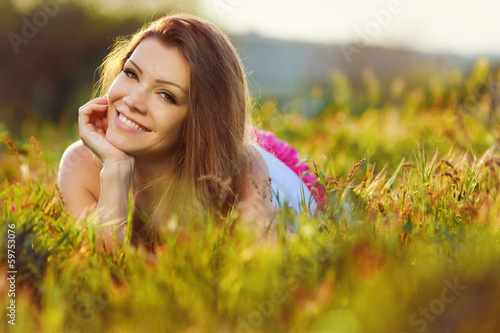 portrait  young woman on the meadow on a warm summer day