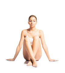 A sporty, fit and beautiful girl meditating isolated on white