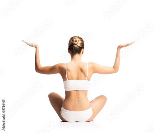 A young and fit woman doing yoga on a white background