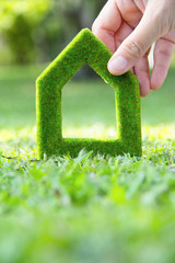 Hand holding green house icon