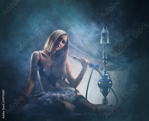 A sexy woman in luxury underwear smoking the hookah