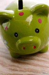 Green piggy bank on a wooden background