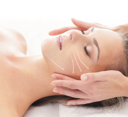 Portrait of a young woman laying on a face massage procedure