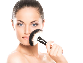 Beauty portrait of a young woman holding a makeup brush