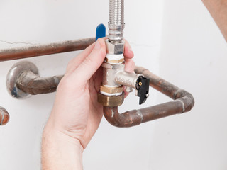 Man repairing a safety valve of an electric boiler