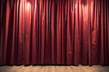 Red theater curtain with a wood stage floor