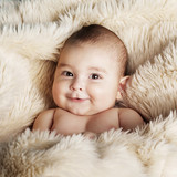 cute happy baby portrait lying on fur