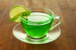Transparent cup of green tea with lime and mint