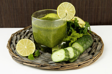 Glass of green vegetable juice and cucumber
