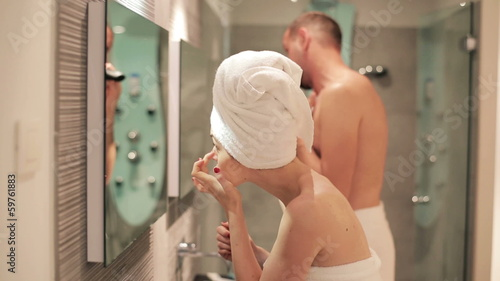 Young couple preparing in front of the mirror in bathroom