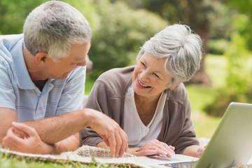Smiling senior couple using laptop at park