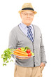 Smiling senior man posing with a dish full of healthy vegetables