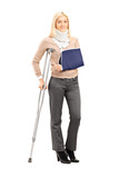 Happy blond female with broken arm holding a crutch posing