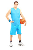 Full length portrait of a male basketball player holding a ball