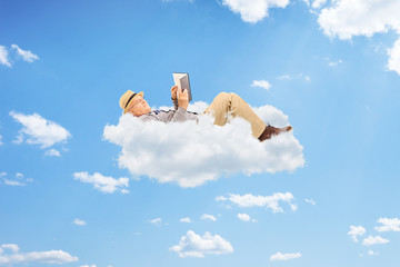 Senior man reading a book on clouds