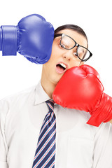 Young man with glasses punched by two boxing gloves