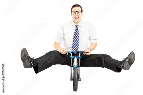 Excited young businessman with tie riding a small bicycle