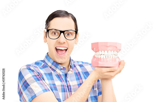 Guy holding dentures made out of plaster cast looking at camera