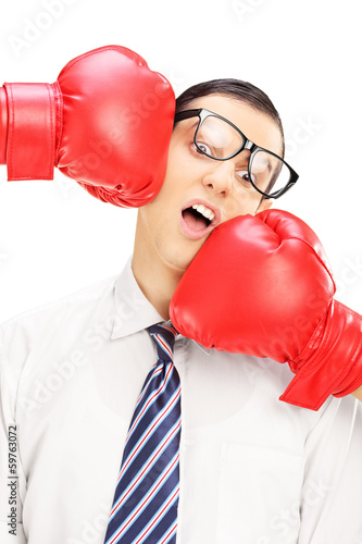 Young man with glasses punched by two red boxing gloves
