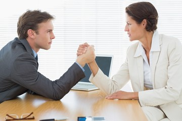 Serious business couple arm wrestling at office desk