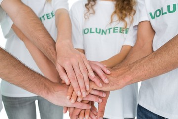 Close-up mid section of volunteers with hands together