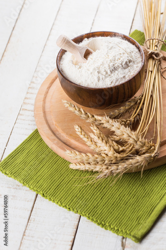 Flour in wooden bowl on table