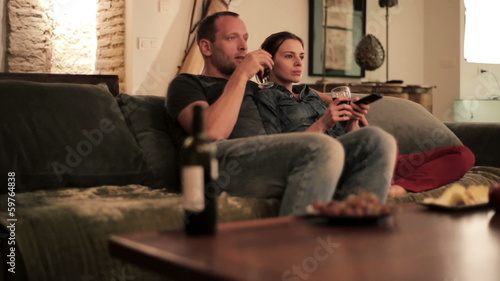 Young couple sitting on sofa and watching tv