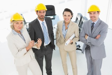 Confident architects with hard hats and blueprint in office