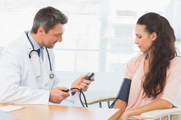 Male doctor checking blood pressure of a woman