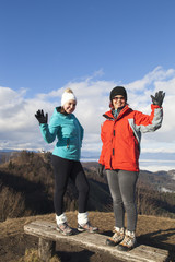 Two happy women hikers waving hello outdoors