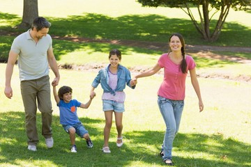 Family of four holding hands and walking at park