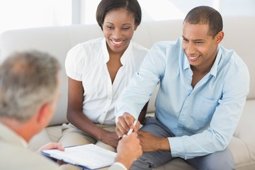 Young smiling couple listening to salesman on the couch