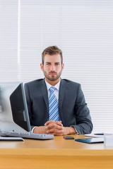 Serious businessman with computer at office desk